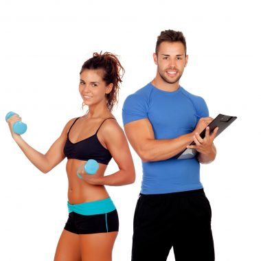 Handsome personal trainer with beautiful girl with dumbbells isolated on white